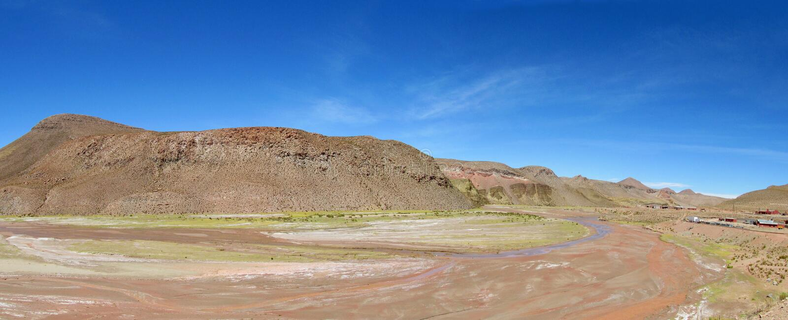 Dry river valley in desert. Altiplano desert valley. Panoramic view of empty dry solty desert soil in dry river canyon. Red rocks stock photo