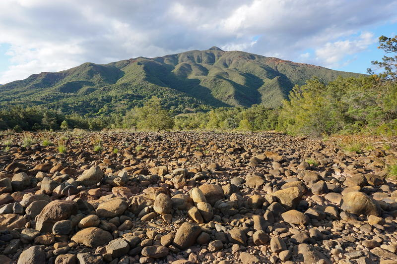 Dry riverbed with rocks New Caledonia. Dry riverbed with rocks and a mountain in background, New Caledonia, Dumbea river, Grande Terre island, south Pacific royalty free stock images