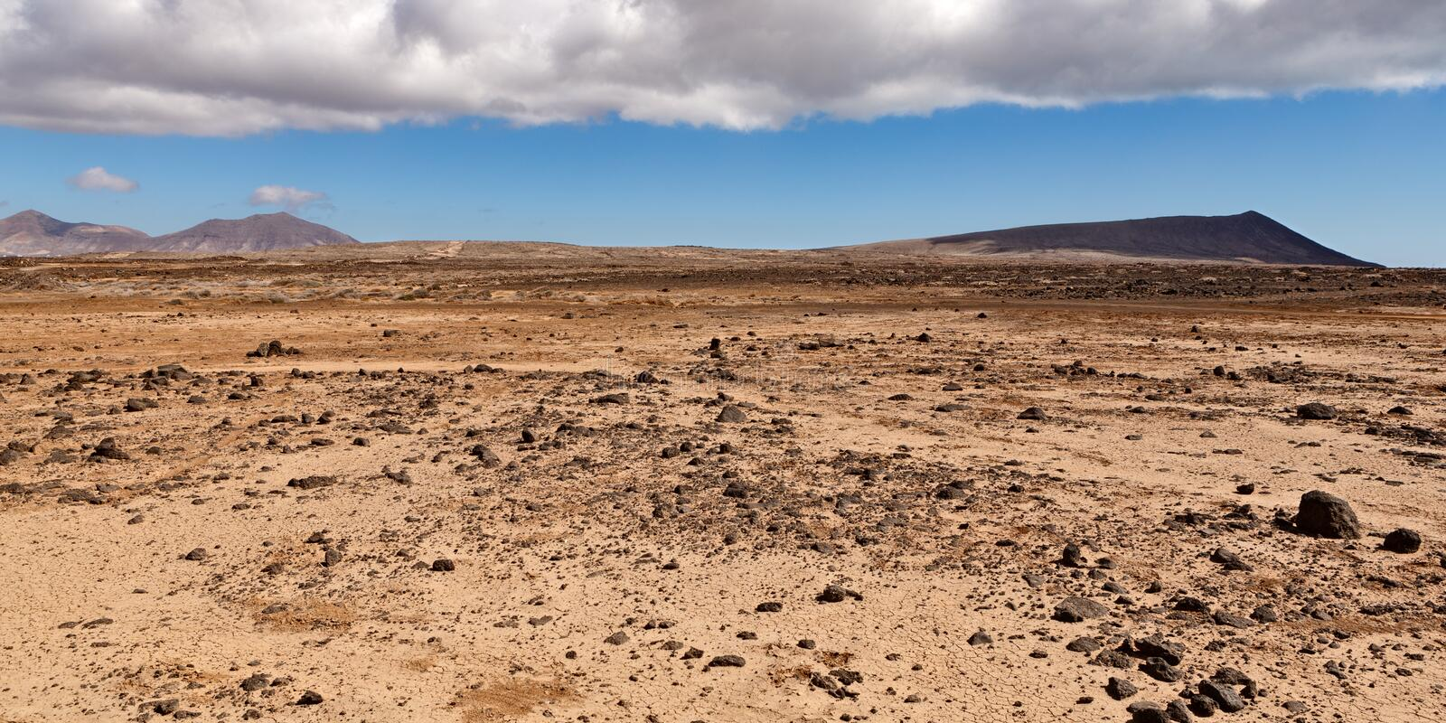 Dry and rocky desert landscape w. Ith some mountains in the distance stock photography