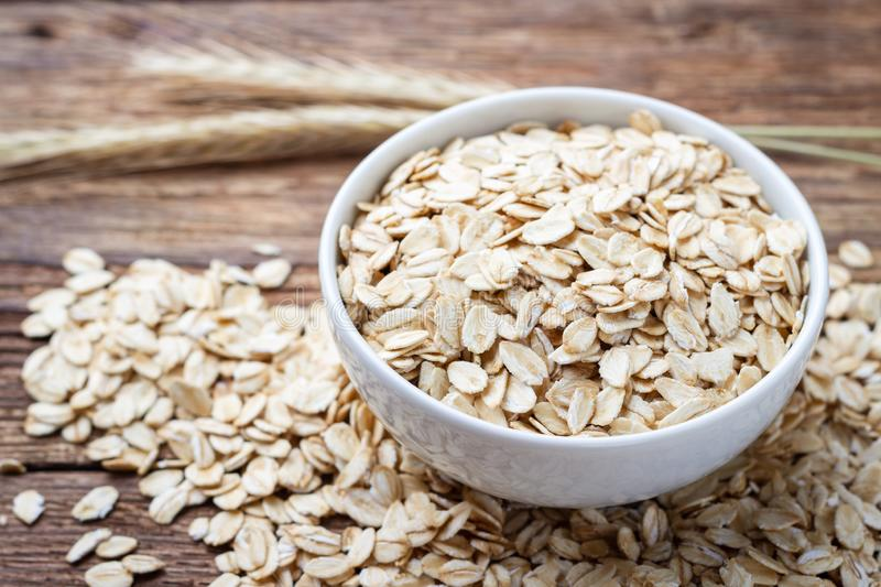 Dry rolled oat flakes oatmeal. On wooden table stock image