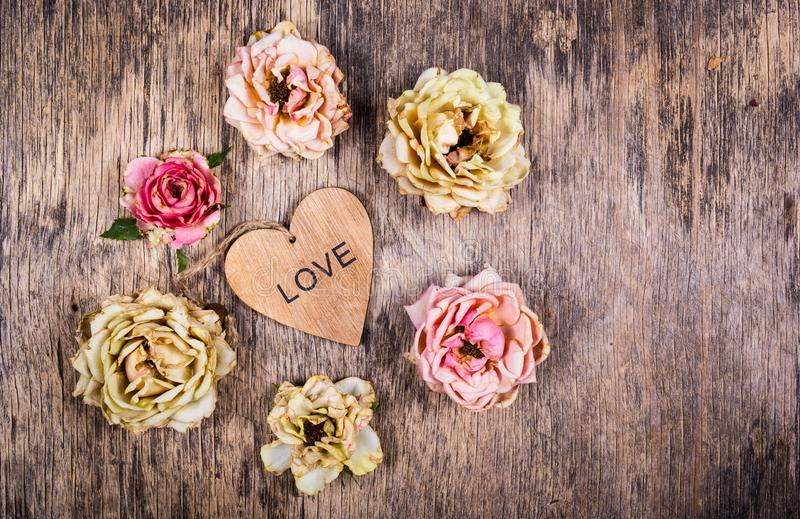 Dry roses and a wooden heart. Dead flowers and love. Romantic concept. Dry roses and a wooden heart. Dead flowers and love royalty free stock image