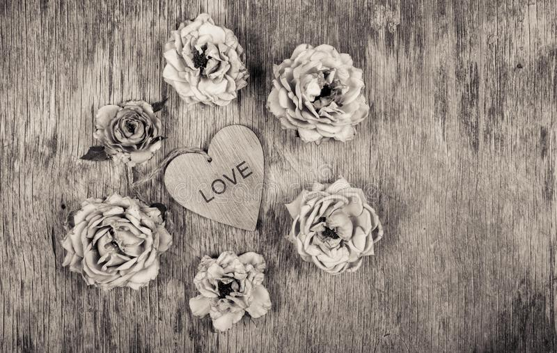 Dry roses and a wooden heart. Dead flowers and love. Romantic concept. Monochrome. Dry roses and a wooden heart. Dead flowers and love. Romantic concept royalty free stock images