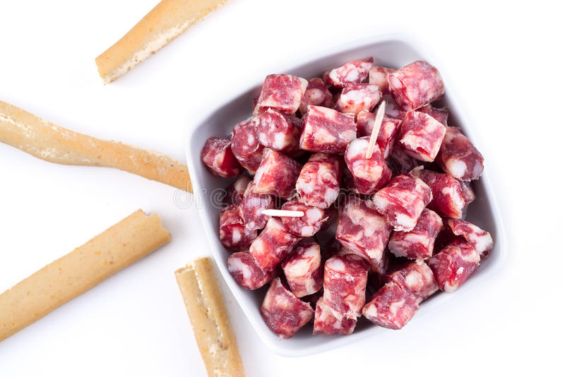 Dry sausage cutted in small pieces in a bowl and bread sticks royalty free stock image