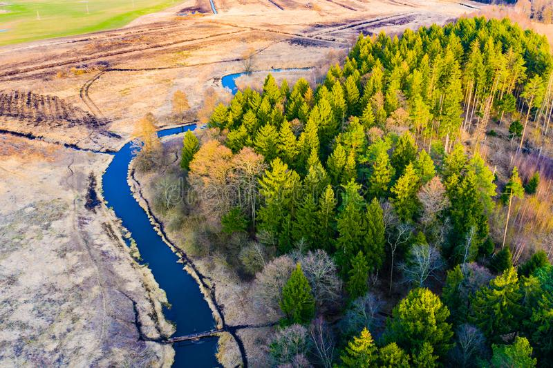 Dry season concept. Mixed forest surrounded by tiny river curves, aerial landscape. Autumn royalty free stock photo