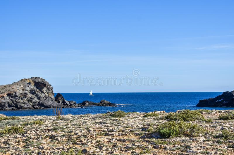The dry semi-desert meets the Mediterranean in southern Spain. The dry semi-desert of southern Spain meets the blue water of the mediterranean with rocks rising stock photography