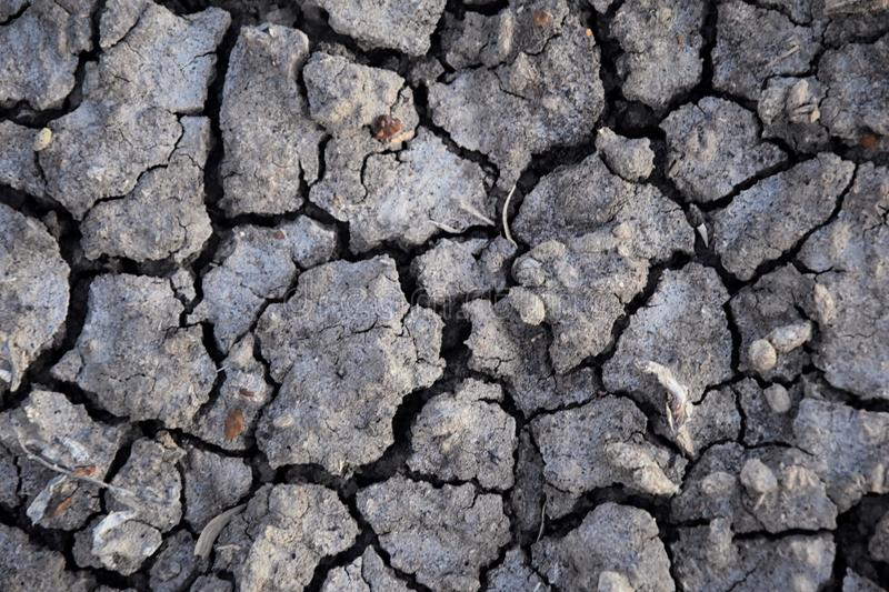 Dry soil abstract background. Drought. Gray dry soil. Soil background. Cracked soil background. Earth pattern. Soil texture. Crack stock photography