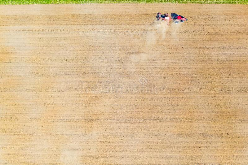 Dry soil background. Rural aerial landscape. Tractor cultivating the farmland stock image