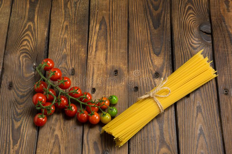 Dry spaghetti and cherry tomatoes on a wooden background royalty free stock images