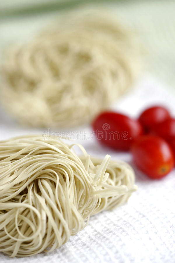 Dry spaghetti and tomato royalty free stock photography