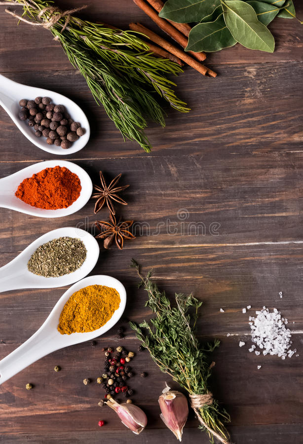Dry spices and green herbs. Dry spices, green herbs, garlic and pepper on the wooden table stock photos
