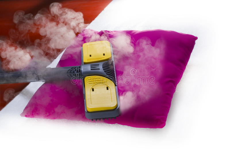 Dry steam cleaner in action. Using dry steam cleaner to sanitize pillow royalty free stock image