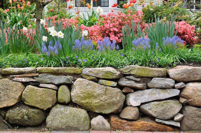Dry Stone Wall and Colorful Garden stock image