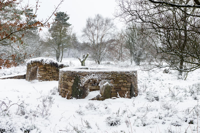 Snow - Dry Stone wall structures - Animal Shelters - North Yorkshire. Drystone walls (or dykes in Scotland) are walls built without any mortar to bind the stones stock image