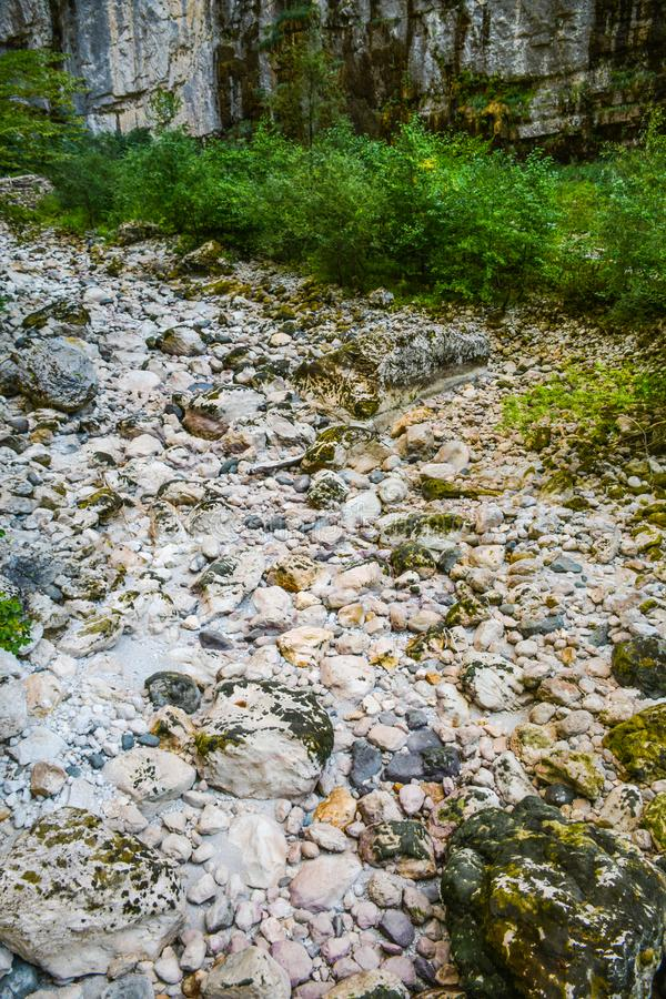 Dry river bed among high mountains royalty free stock photo