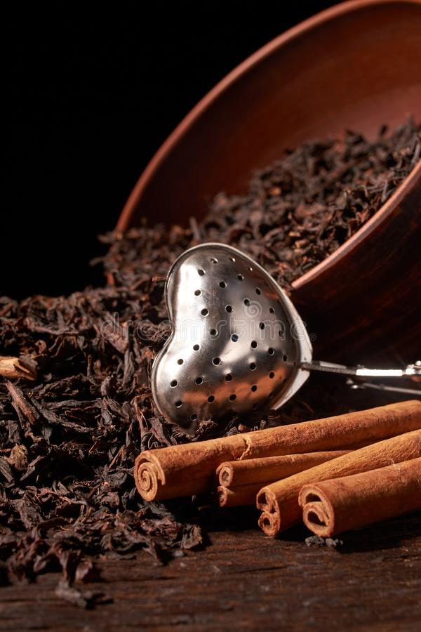 Dry tea leaves in clay bowl on black background. selective focus stock photo