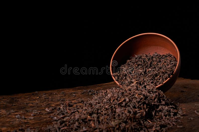 Dry tea leaves in clay bowl on black background. selective focus royalty free stock photos
