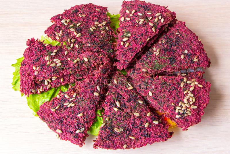 Dry vegan bread loaves on green lettuce leaves on plate on table. Bread, cooked by dehydrating. Ingredients: beetroot, garlic, flax, walnut, dill, sesame,seeds stock image