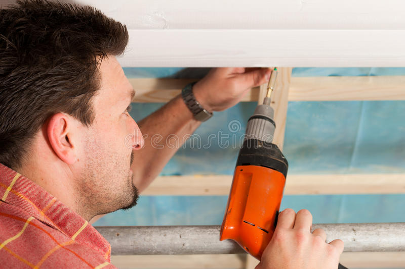 Dry waller with cordless screwdriver. Man doing dry walling, working under a roof slope royalty free stock photo
