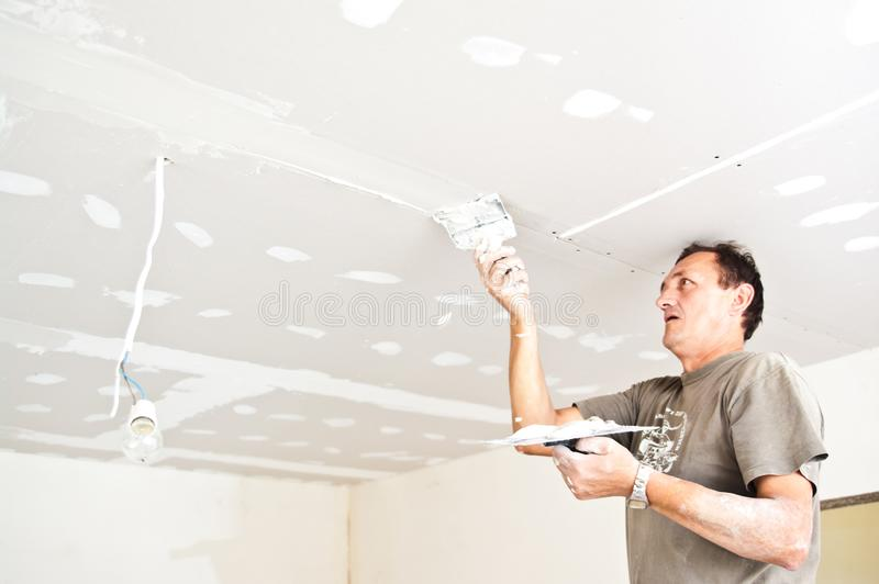 Dry waller working at the ceiling royalty free stock image