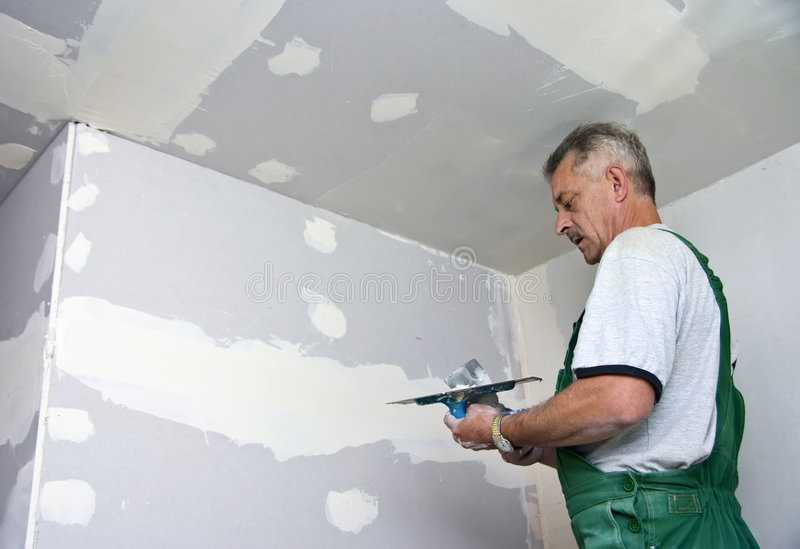 Dry waller at work. A dry waller standing on a ladder high at the ceiling, putting plaster on the walls with a special tool royalty free stock image
