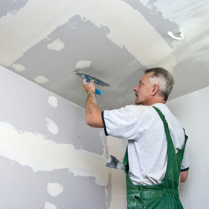 Dry waller at work. A dry waller standing on a ladder high at the ceiling, putting plaster on the walls with a special tool stock image