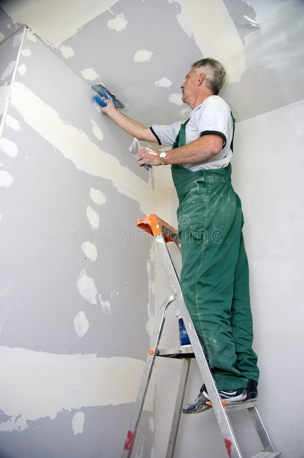 Dry waller at work. A dry waller standing on a ladder high at the ceiling, putting plaster on the walls with a special tool royalty free stock photography