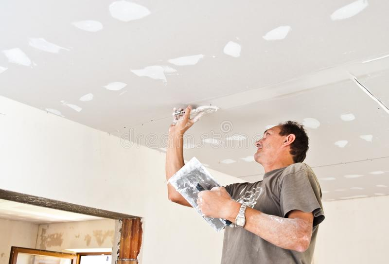 Dry waller working at the ceiling stock photos