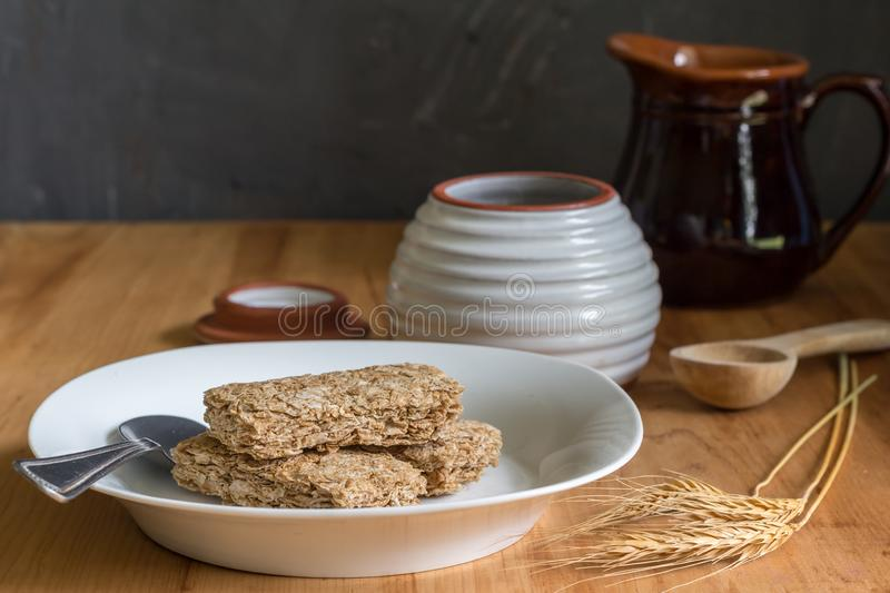 Dry wheat cereal bars  in breakfast plate on wooden table with wheat ears in foreground and honey and milk jar in background. Wheat cereal bars dry in breakfast royalty free stock photography
