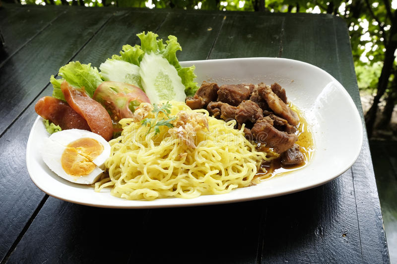Dry Yellow Noodles with egg, salad, sausage and braised pork. Dry Yellow Noodles with egg salad sausage and braised pork stock photo