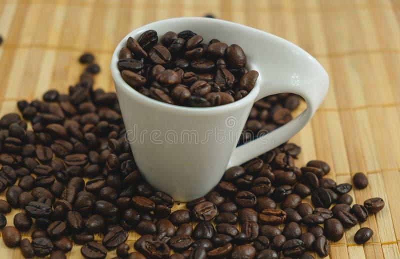 Dryckbakgrundskopp med stället för kaffeböna på trätabell w arkivfoto