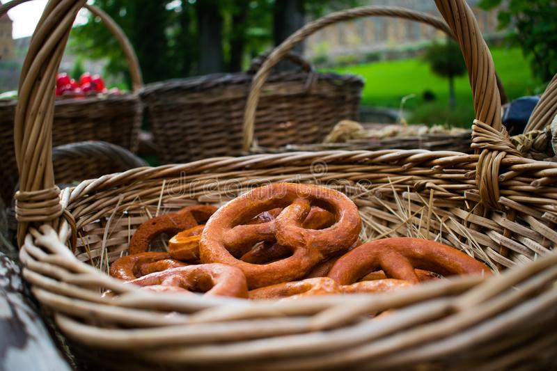 Dryers, bagels, golden baked and sweet round buns with poppies in the form of rings in wicker baskets made from a vine. Appetizing stock image