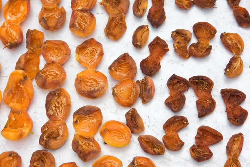 Drying apricot in the sun. Apricot halves are spread out on a metal sheet and dried in the sun. Close-up. Summer. outdoor stock photography