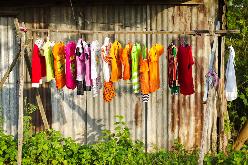 Drying colorful baby`s clothes. In daylight royalty free stock photography