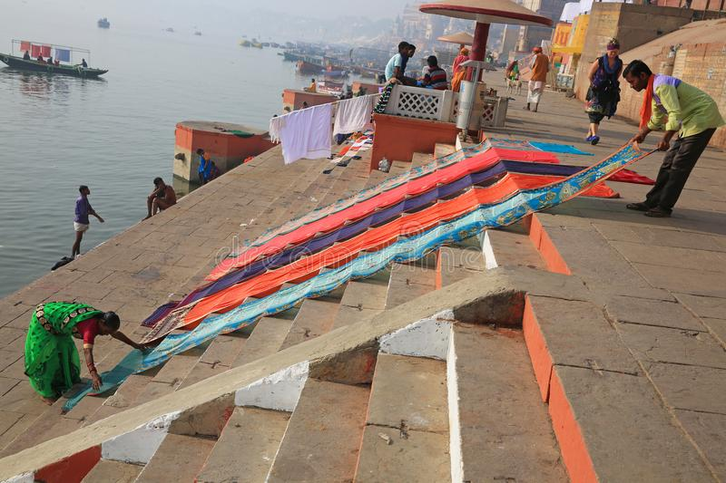 Drying Colorful Garments on the Bank of the Ganges. Two individuals spread out colorful garments to dry on the banks of the Ganges River in Varanasi, India stock photos