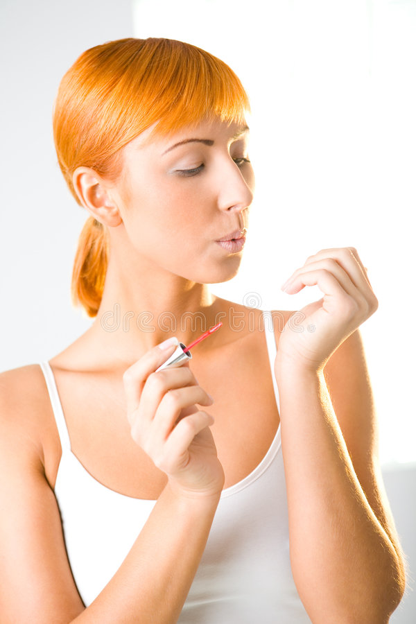 Drying fingernails. Young woman painting fingernails with red nail varnish. She's blowing on nails. Front view stock images