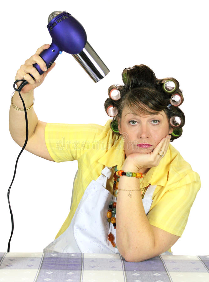 Drying Hair Housewife. Totally bored frumpy housewife with hair rollers dries her hair stock photos