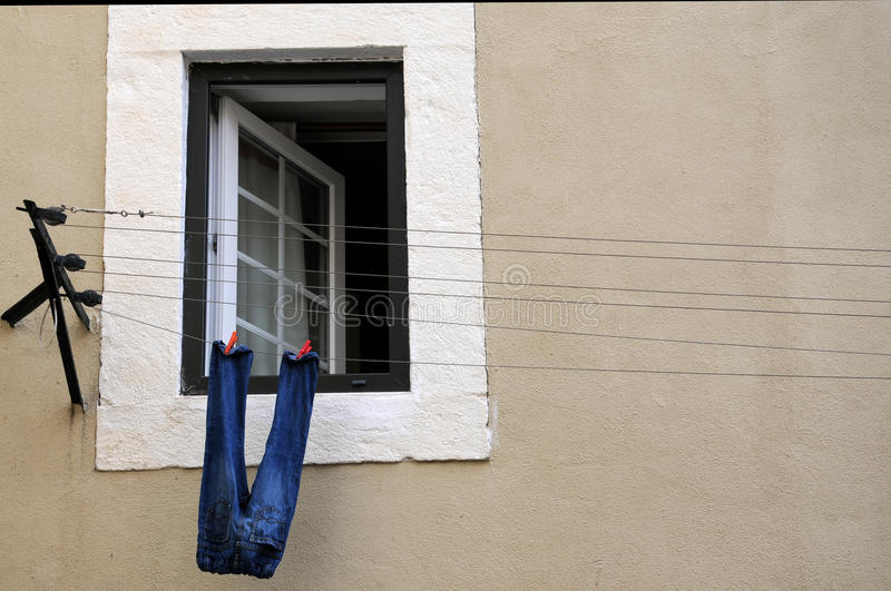 Drying laundry. Jeans drying outside at a line between the windows royalty free stock images