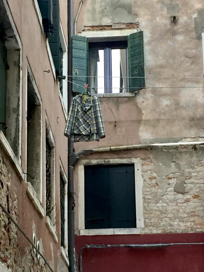 Drying out. A lone plaid jacket hanging outside a courtyard widow in Venice royalty free stock photography