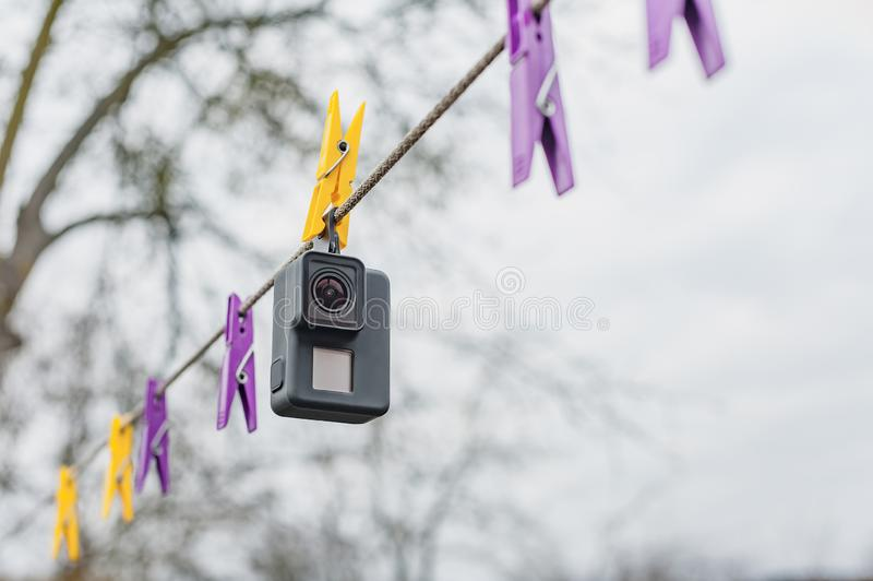 Drying waterproof Action Camera on clothespins, against the sky. royalty free stock image