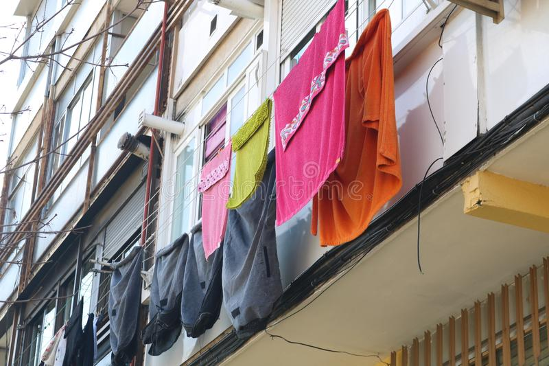 Drying wet clothes hanging on wires after laundry stock photo