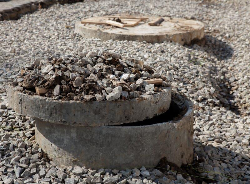 drymba lągi naprawia drogi Otwartego bez zabezpieczenia ściekowego manhole w ulicie obraz stock