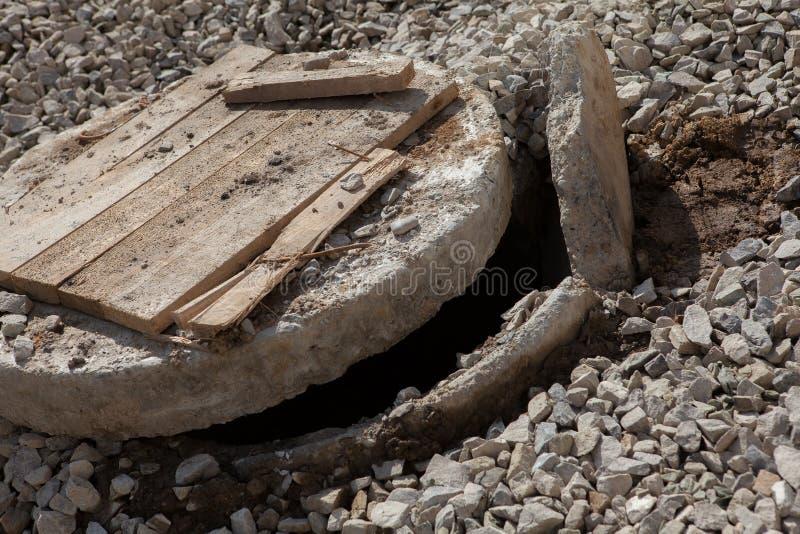 drymba lągi naprawia drogi Otwartego bez zabezpieczenia ściekowego manhole w ulicie obrazy stock