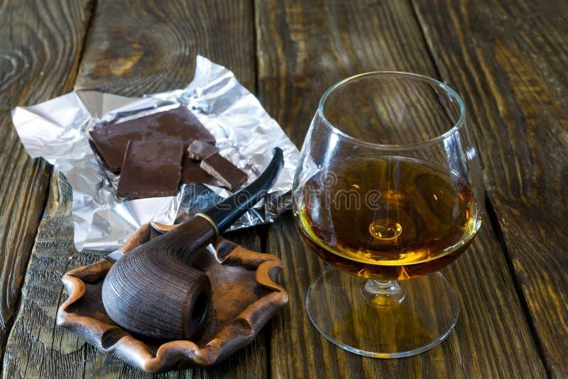 Drymba w ashtray, szkło koniak i zmrok czekolada na textured dębowym stole obrazy stock