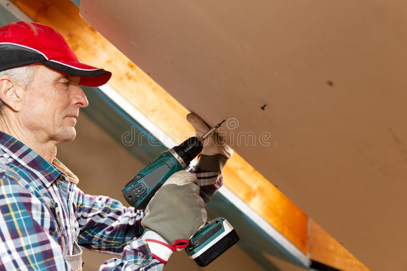 Drywall construction, attic renovation. Man fixing drywall suspended ceiling to metal frame using electrical screwdriver royalty free stock photo
