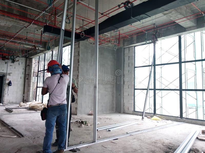 Drywallinstallationsarbete som är pågående vid byggnadsarbetare på konstruktionsplatsen royaltyfri foto