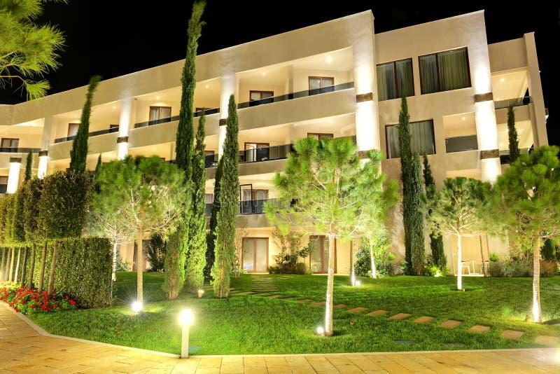 Drzewa w nocy iluminaci przy luksusowym hotelem fotografia stock