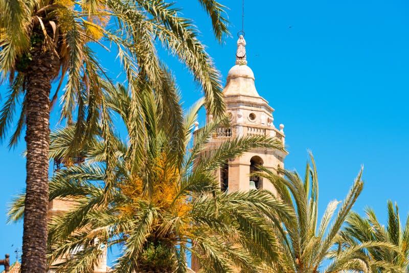 Drzewka palmowego zakończenie w tle, wierza kościół Sant Bartomeu i Santa Tecla w Sitges, Barcelona, Hiszpania zdjęcia stock