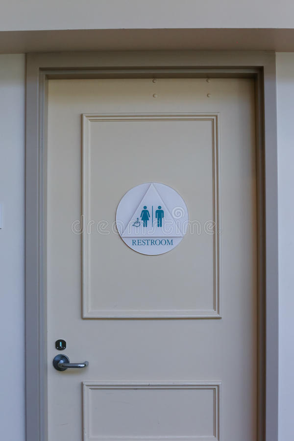 Drzwi z toaleta szyldowym pokazuje wózkiem inwalidzkim, kobietą i mężczyzna, obrazy stock