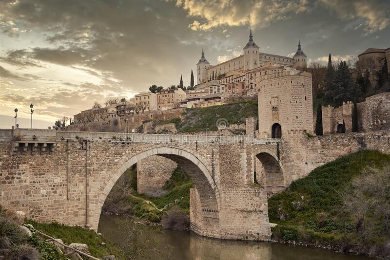 Toledo in Spain with Tagus River and Roman bridge Puente de Alcantara. royalty free stock images