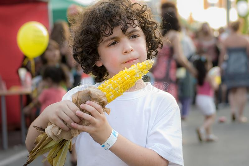 Child boy eating a corn on the cob in a street festival royalty free stock photos